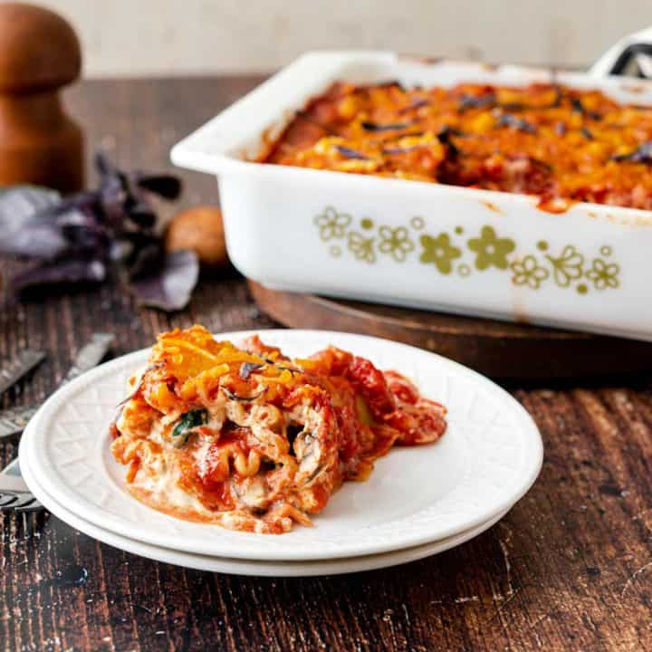 White plate with a lasagna roll on it, with casserole dish in background
