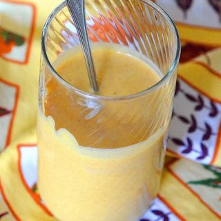 Pumpkin Protein Smoothie in a glass with spoon on a fall-themed linen