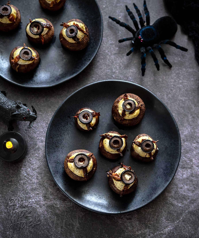 Tofu-Stuffed mushrooms on black plates with halloween decorations
