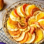 Layered fruit tart in a glass pie dish on a cooling rack