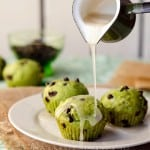Glaze being poured over green-hued, chocolate chip cupcakes on a white plate