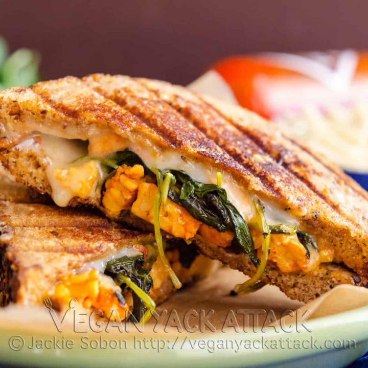 An nontraditional Grilled Buffalo Tempeh Mozzarella Sandwich, complete with spicy tempeh, kale, and melty vegan mozzarella.