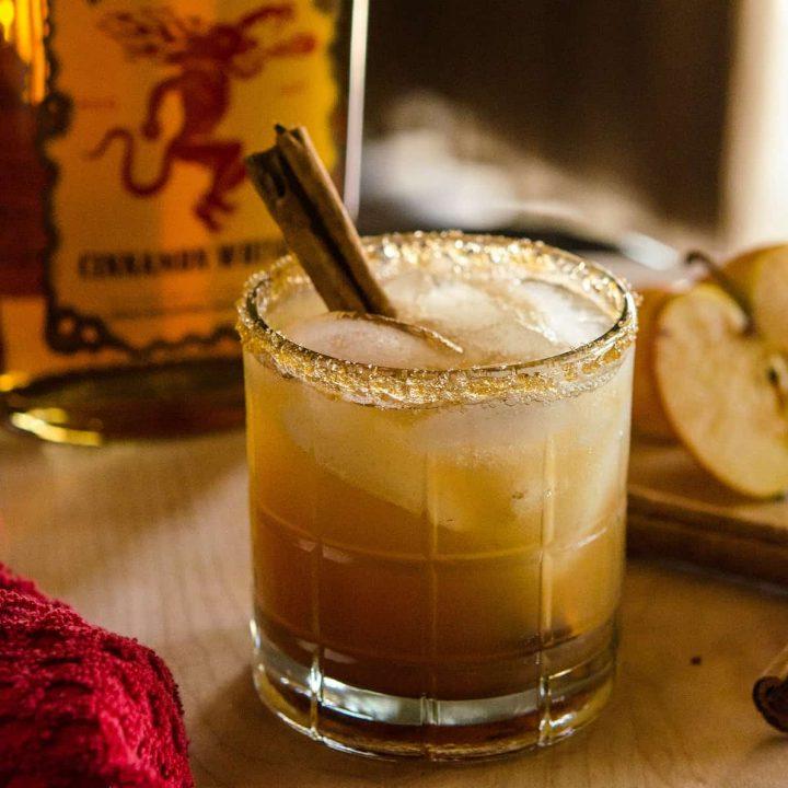Image of apple juice-based cocktail with cinnamon stick garnish