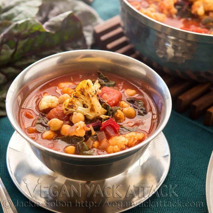 Bowls of cauliflower soup next to a pot, on a deep teal linen