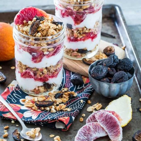 Vanilla Almond Fig Granola Parfaits with Blood Oranges in two jars on a baking sheet