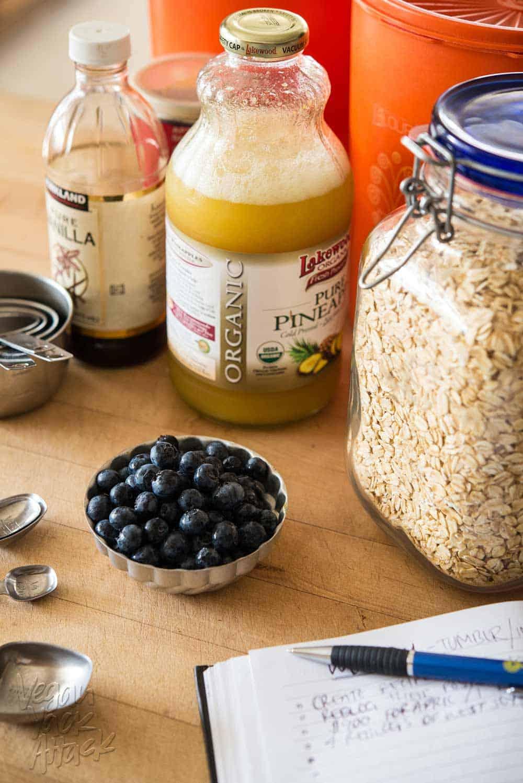 Pineapple juice, oats, vanilla, and blueberries on a kitchen island