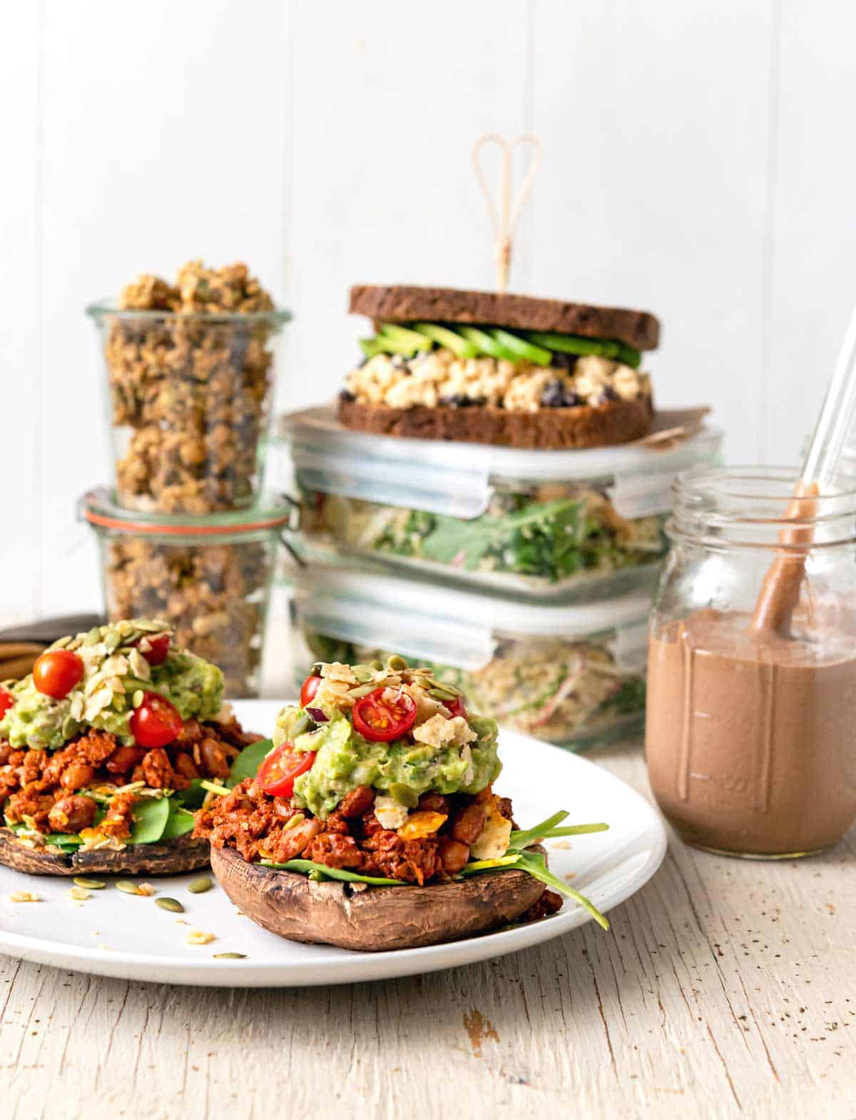 Image of multiple dishes for a High-Protein Vegan Meal Prep for two menu, with stuffed mushrooms in the foreground