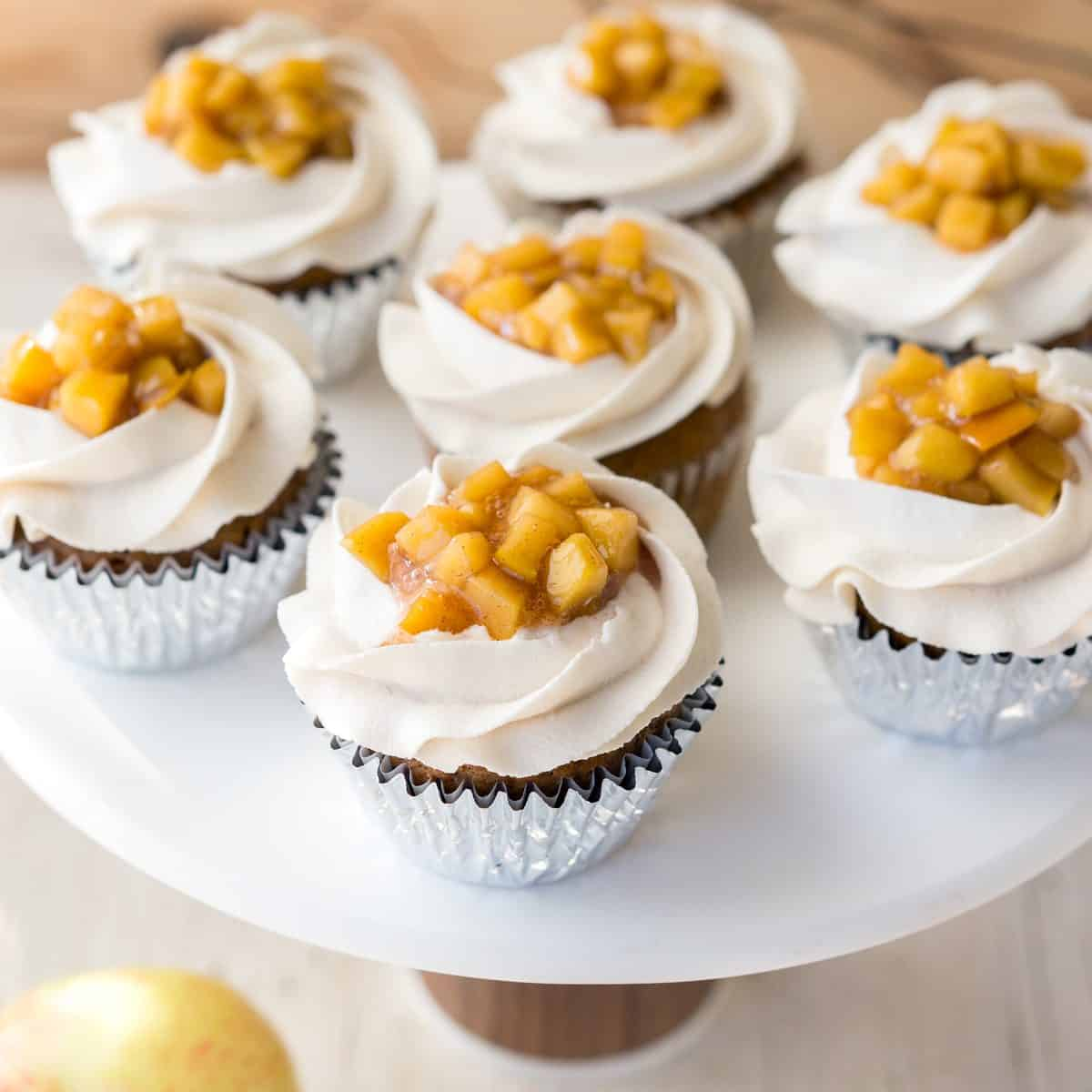 Image of cupcakes on a cake stand with apple pie filling in the middle of vanilla frosting