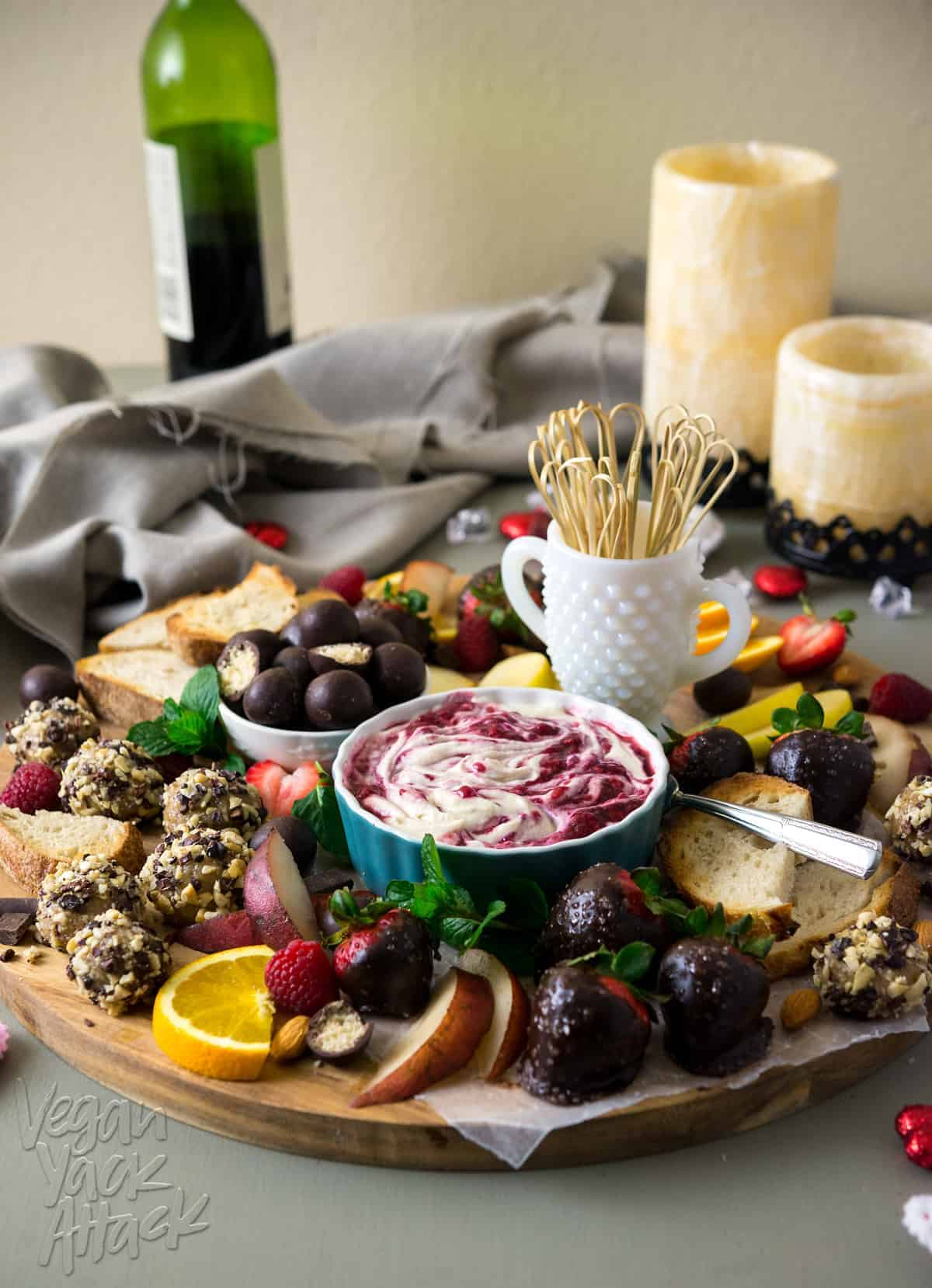 Image of elaborate dessert platter, featuring vegan sweets, raspberry merlot creme fraiche, with wine and candles in the background