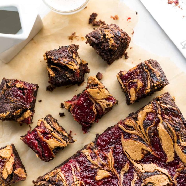 Image of brownies on parchment paper, with peanut butter and jelly swirled into the tops