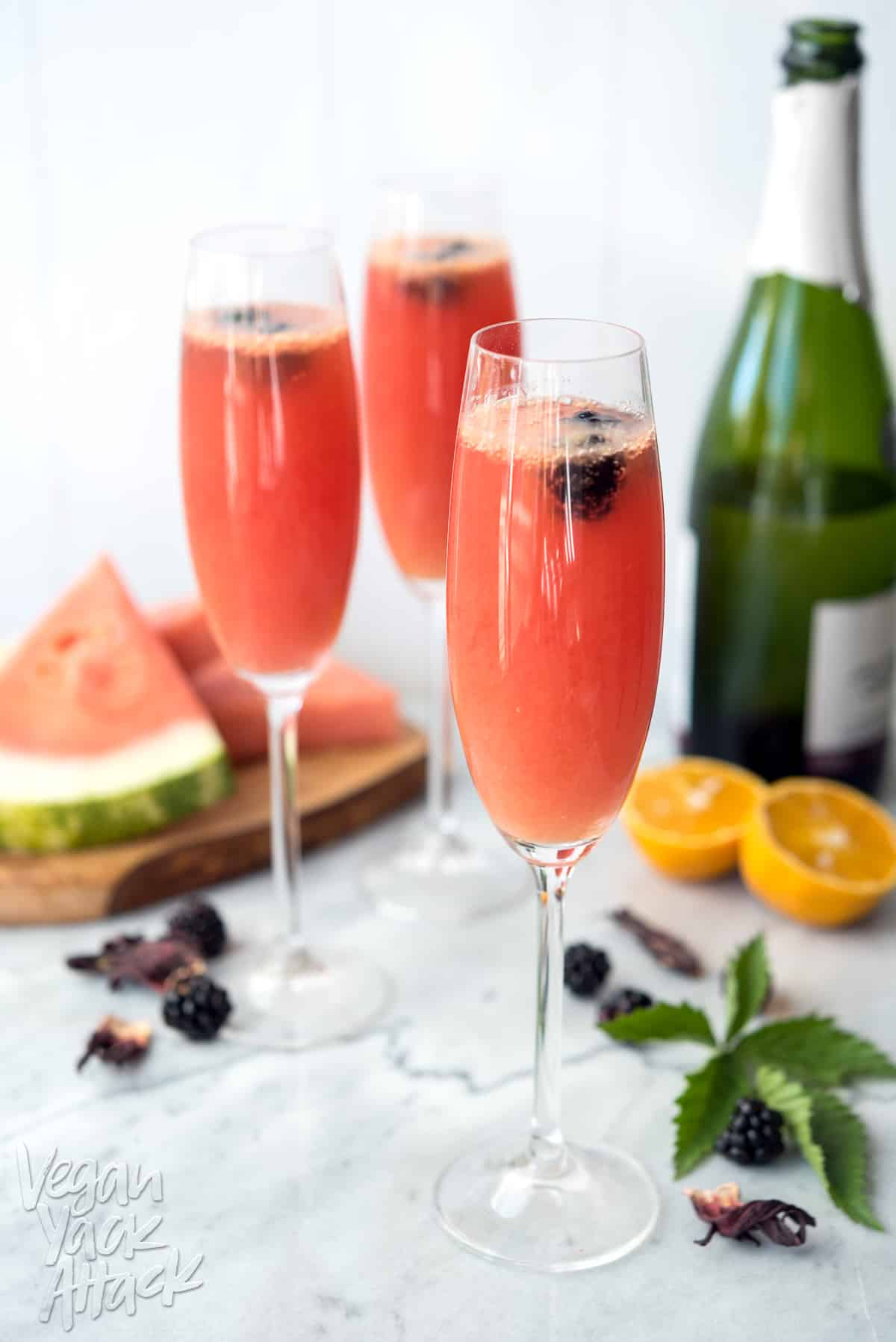 Image of three Champagne glasses filled with watermelon hibiscus mimosas, on a marble table top, surrounded by ingredients.