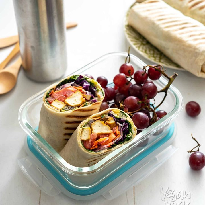 A chipotle tofu rainbow wrap cut in half in a lunch container with grapes
