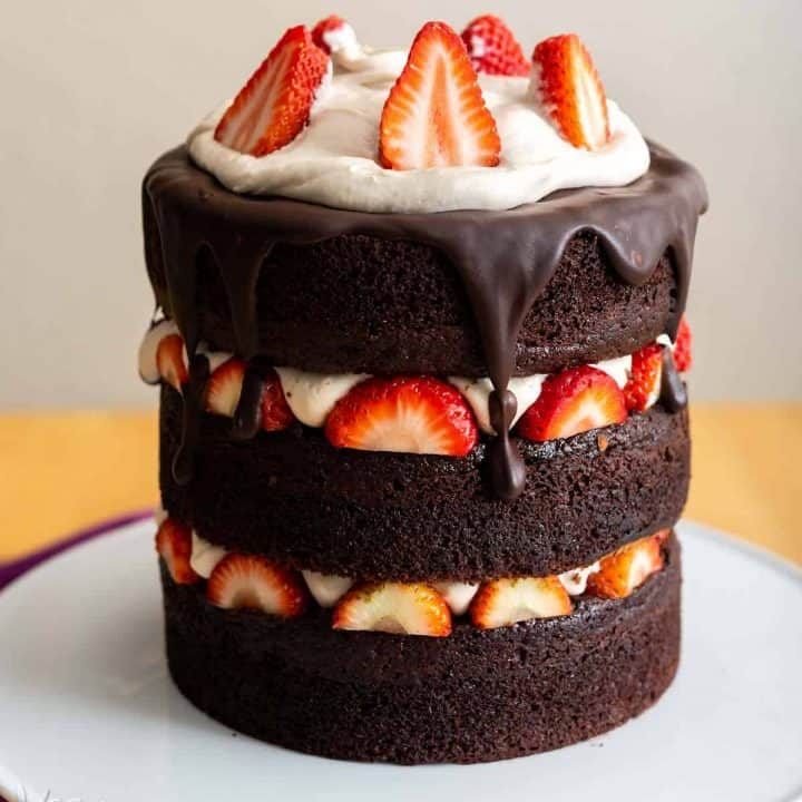 Image of chocolate layer cake with strawberries and vanilla mousse on a white cake stand