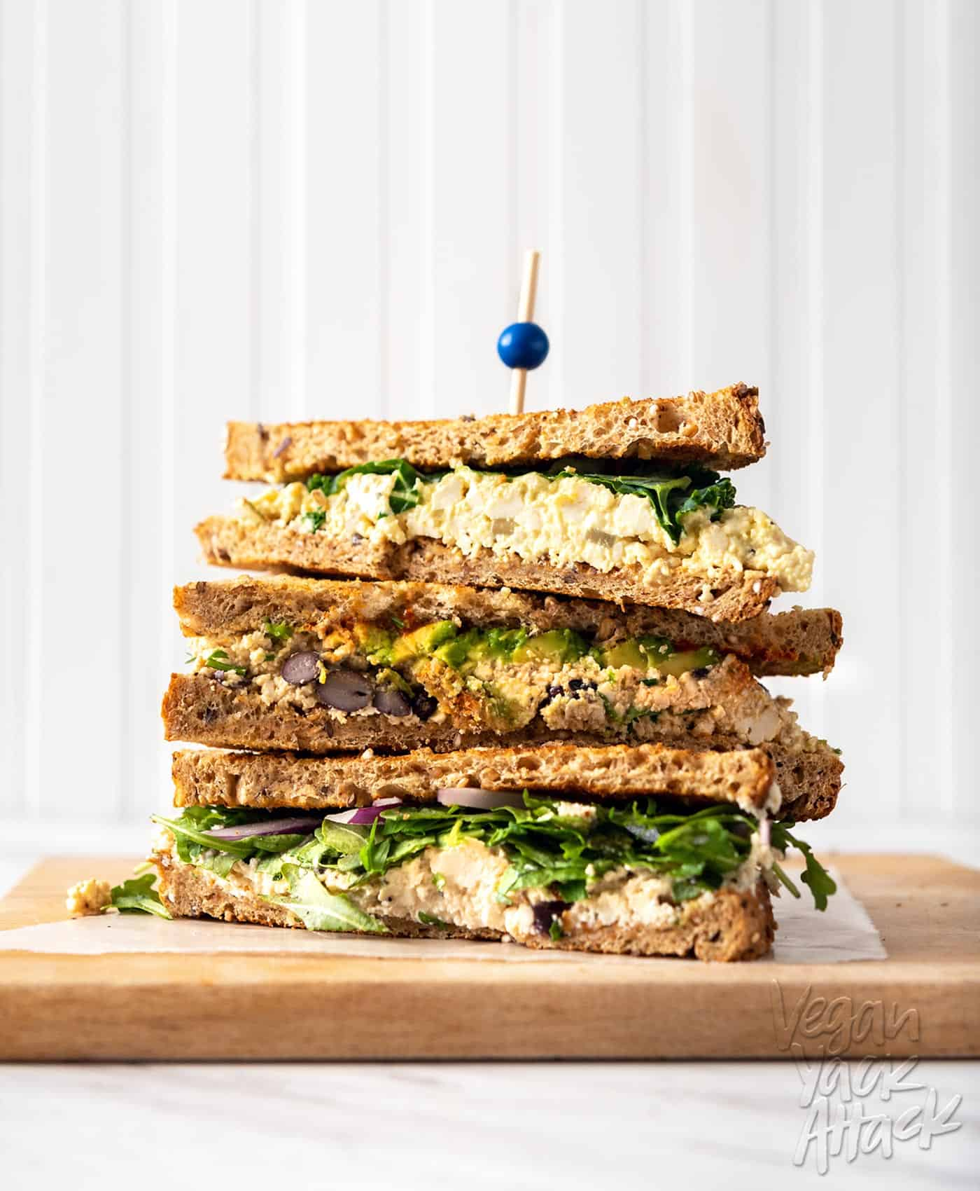 Three tofu egg salad sandwiches stacked on top of one another, on top of a wood board, against a white background
