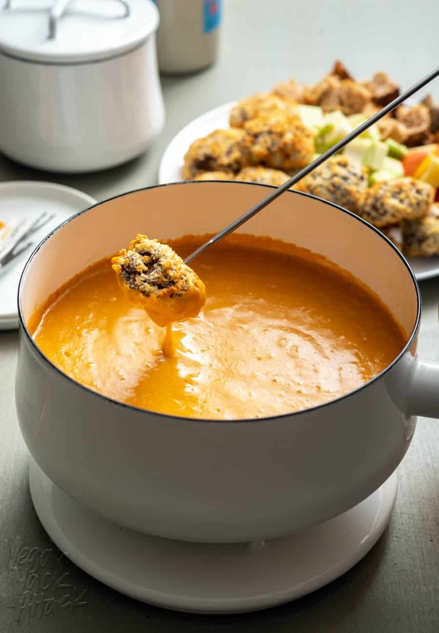 A white pot filled with orange vegan fondue, and a breaded mushroom being dipped into it.