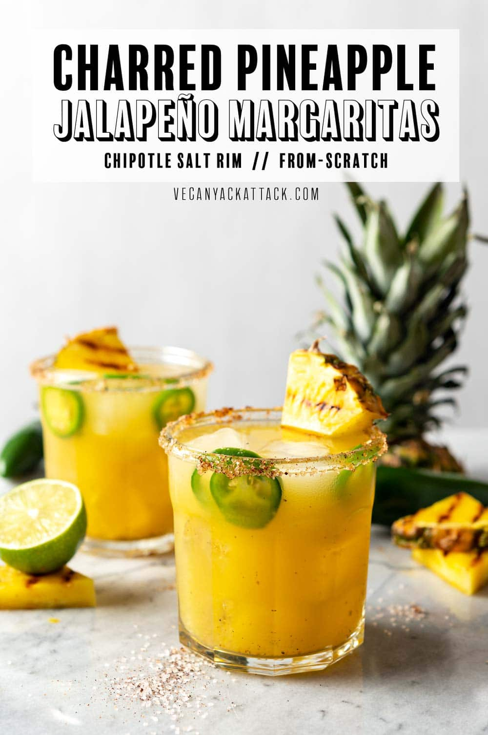 """Two glasses filled with Pineapple Margarita, with fresh jalapeños, grilled pineapple wedge garnish, and chili-salt rim. Text at top reads """"Charred Pineapple Jalapeno Margaritas."""""""