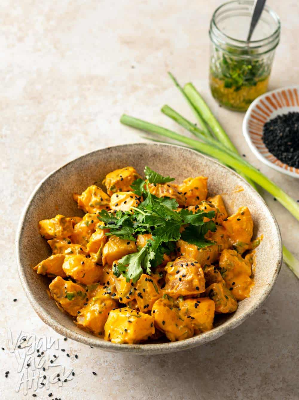 Large ceramic bowl filled with sriracha potato salad that is topped with sesame seeds and cilantro