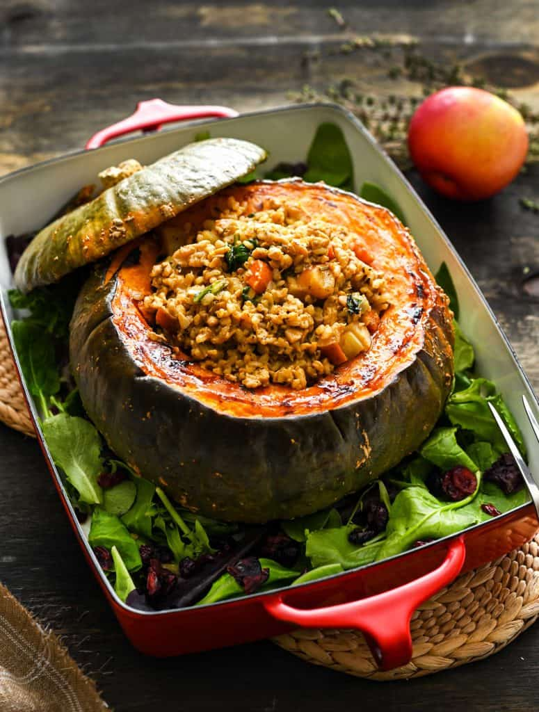 A large, roasted kabocha squash centerpiece, in a casserole dish, stuffed with a rice/tempeh mixture, on a dark background.