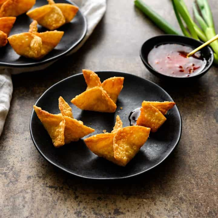 Vegan Crab Rangoon on black plates with a side of sweet chili sauce, whole green onions, and a white linen on a great background