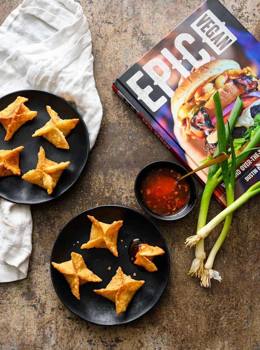Vegan Crab Rangoon on black plates with a side of sweet chili sauce, whole green onions, and a white linen on a grey background, with the Epic Vegan Cookbook.