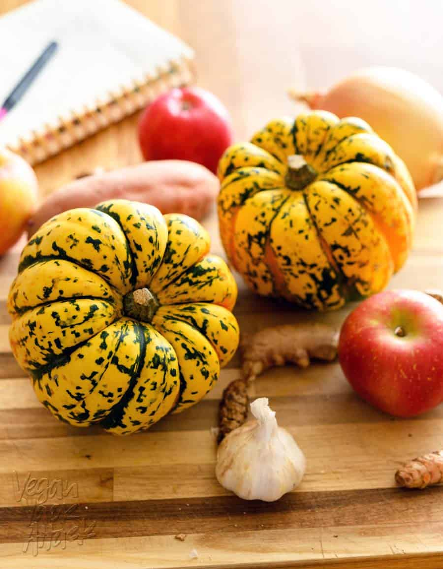 two acorn squash on a cutting board with apples, turmeric, ginger, and garlic