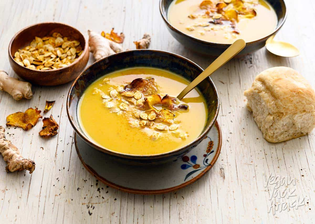 Two bowls of ginger turmeric squash soup with toasted seeds and a bread roll