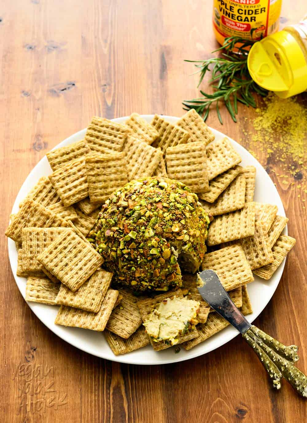 Vegan cheese ball, crusted with chopped pistachios, on a plate, surrounded by wheat crackers.