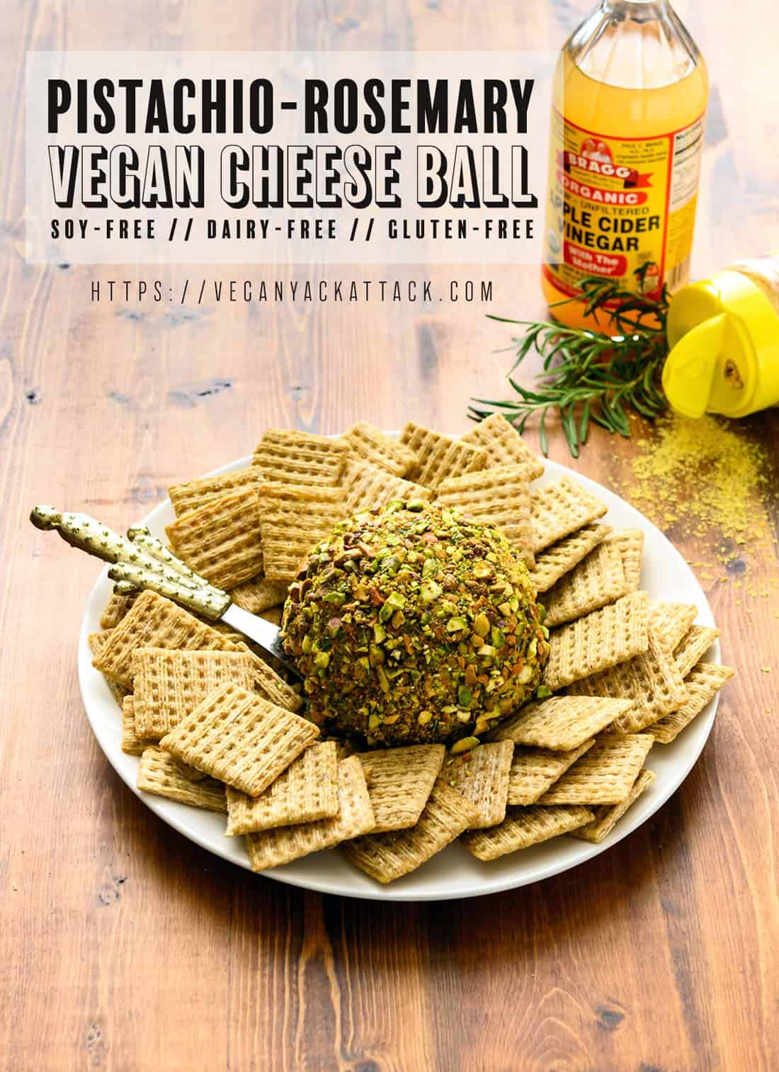 Picture of pistachio-rosemary cheese ball on a plate surrounded by crackers