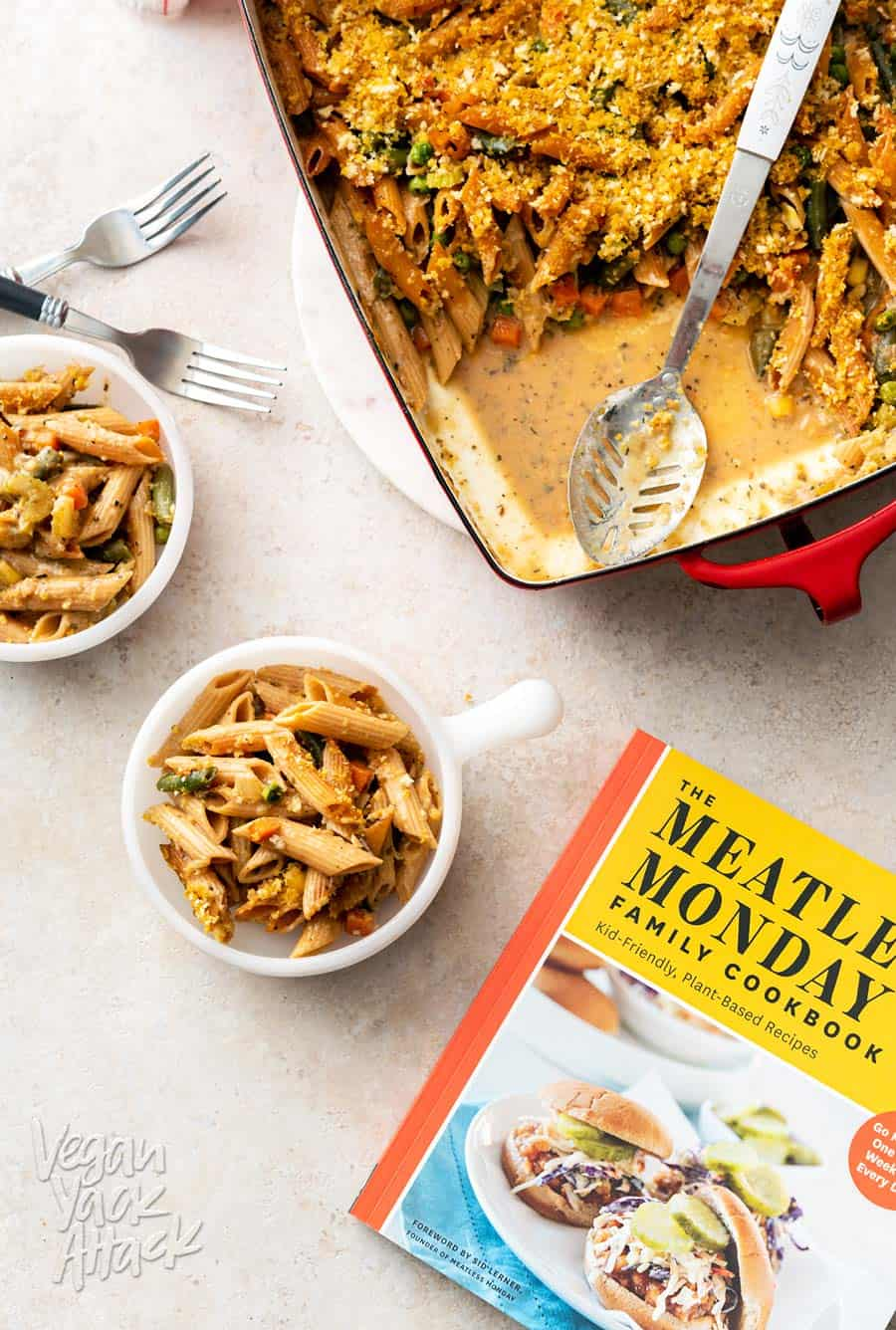 A photo of two bowls filled with vegan noodle casserole, next to a casserole dish and cookbook.