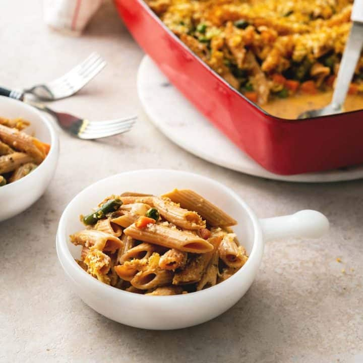 A photo of two bowls filled with vegan noodle casserole, next to a casserole dish.