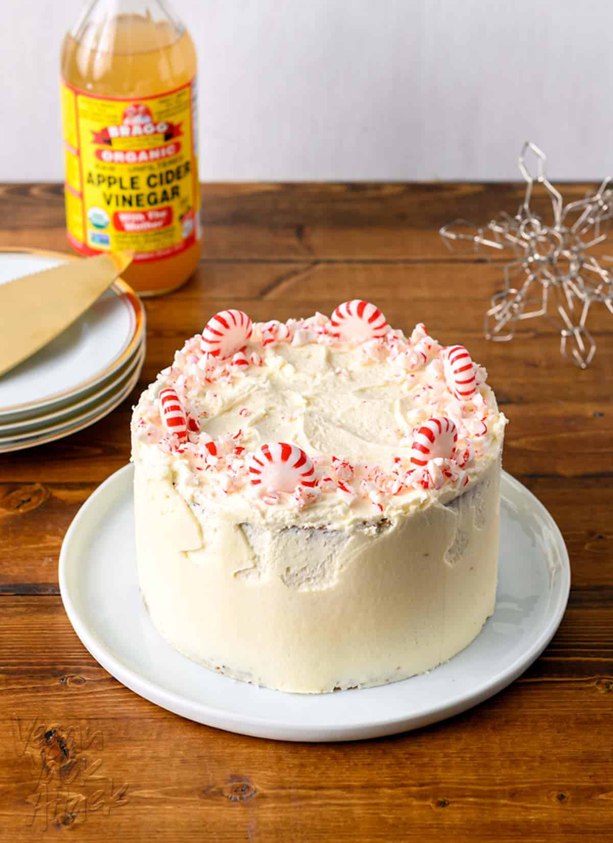 Image of small, layered cake with peppermints on top, serving plates and apple cider vinegar beside it.