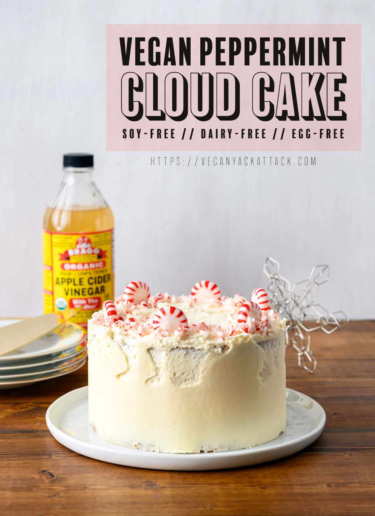 Image of small, layered cake with peppermints on top, serving plates and apple cider vinegar beside it. Text overlay reads: Vegan Peppermint Cloud Cake