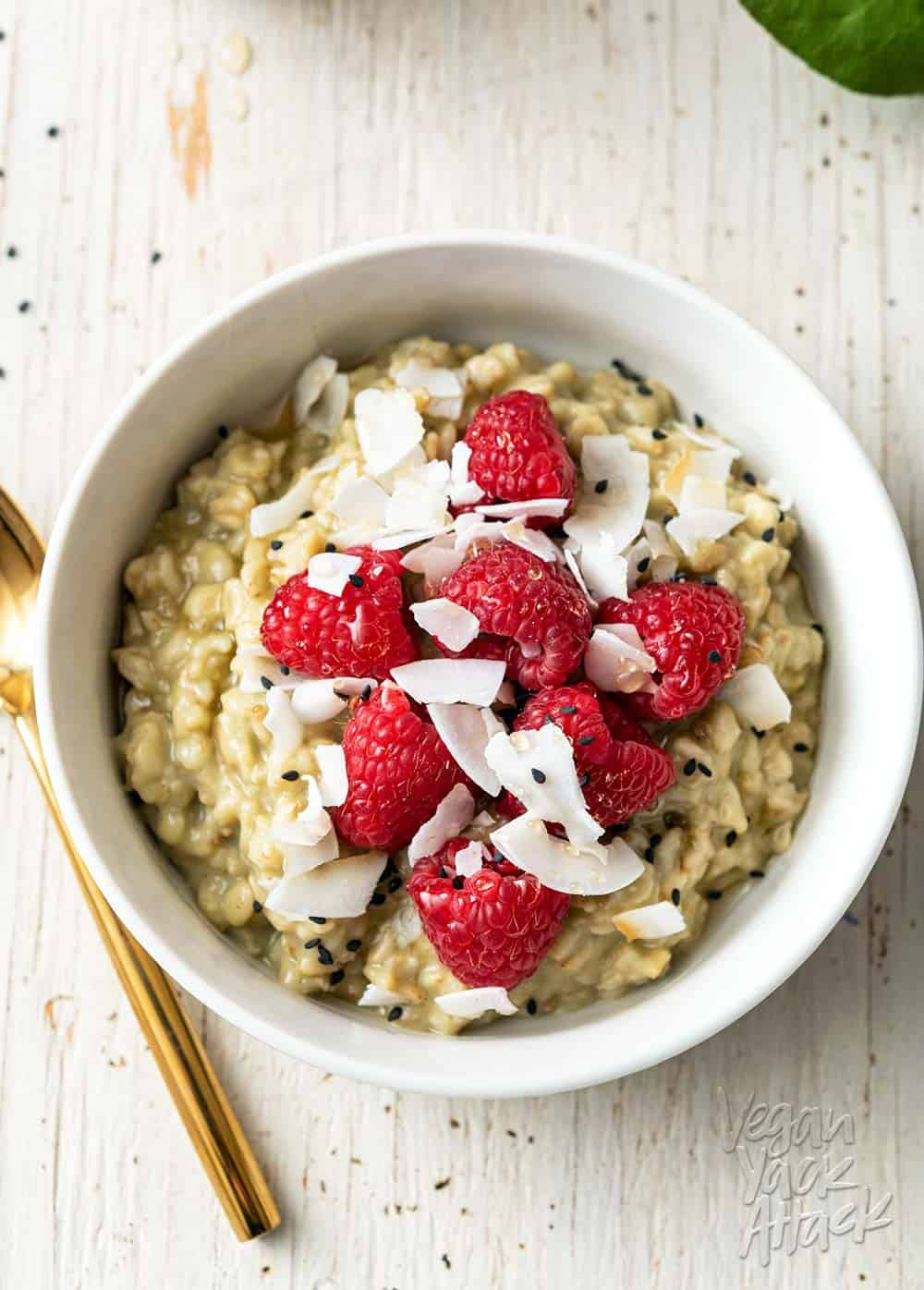 Image of white bowl with matcha oatmeal, topped with raspberries, on a white wood background