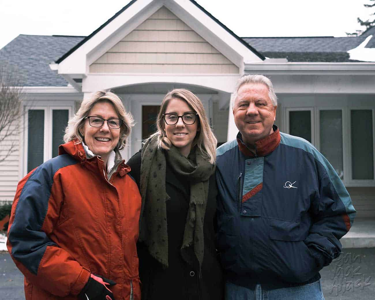 Three people pictured in front of a house in Michigan