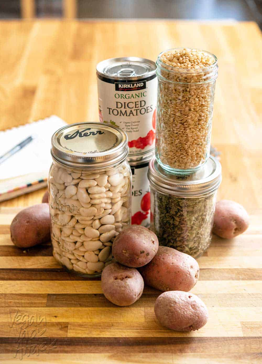 Picture of dried lima beans, red potatoes, canned tomatoes and rice, on a cutting board