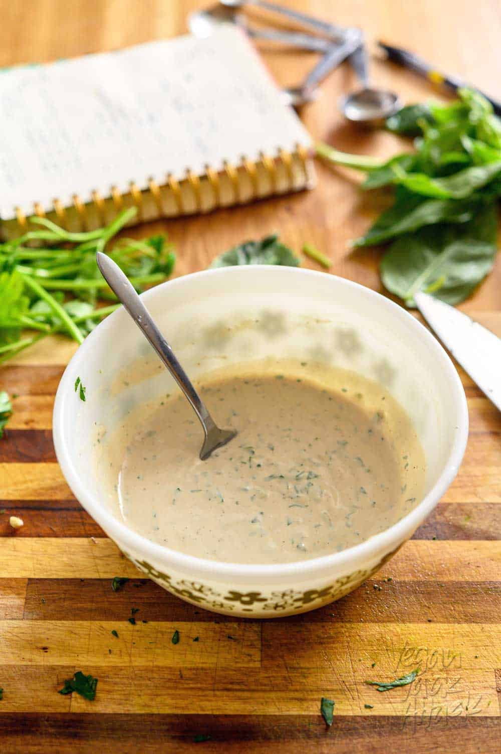 Image of mixing bowl filled with herbed tahini sauce on a cutting board
