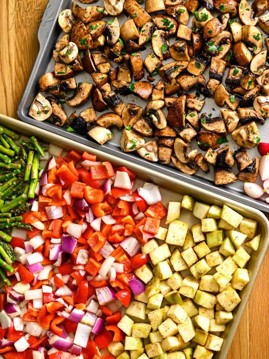 Two sheet pans with raw mushrooms and different vegetables spread across them