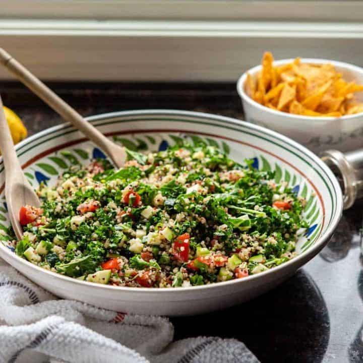 Image of kale quinoa tabbouleh salad in a large ceramic bowl, on granite countertop.