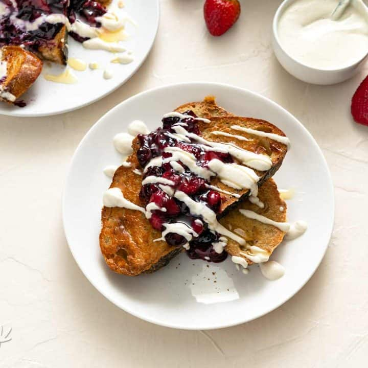 Image of two plates of berry sourdough French toast on an off-white background with cream sauce