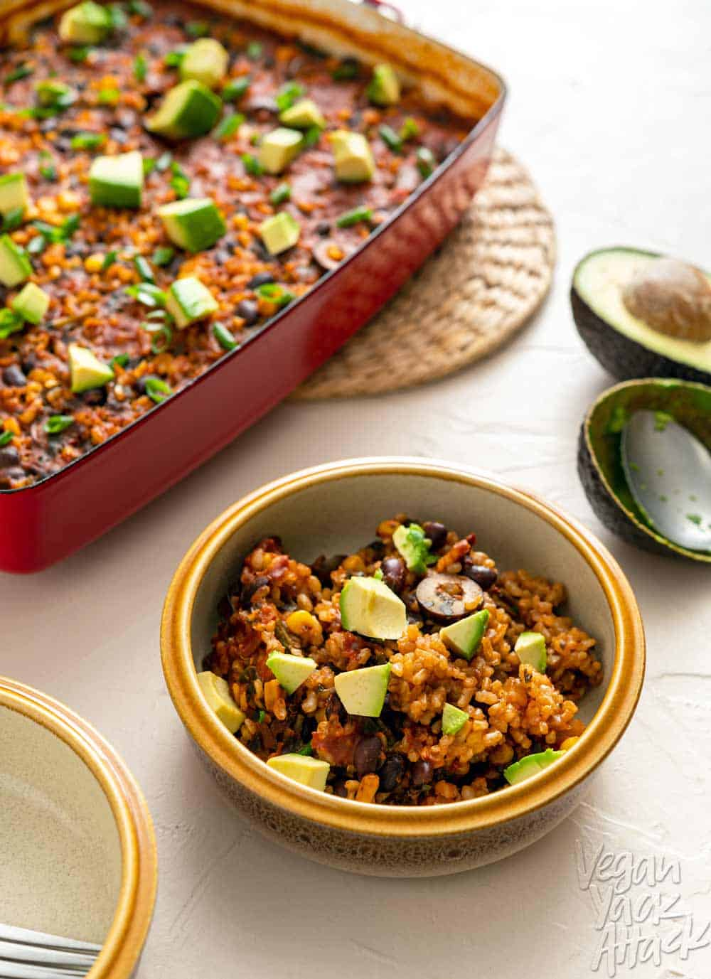 Image of chipotle brown rice bake in a red casserole dish on a beige background with bowl in foreground