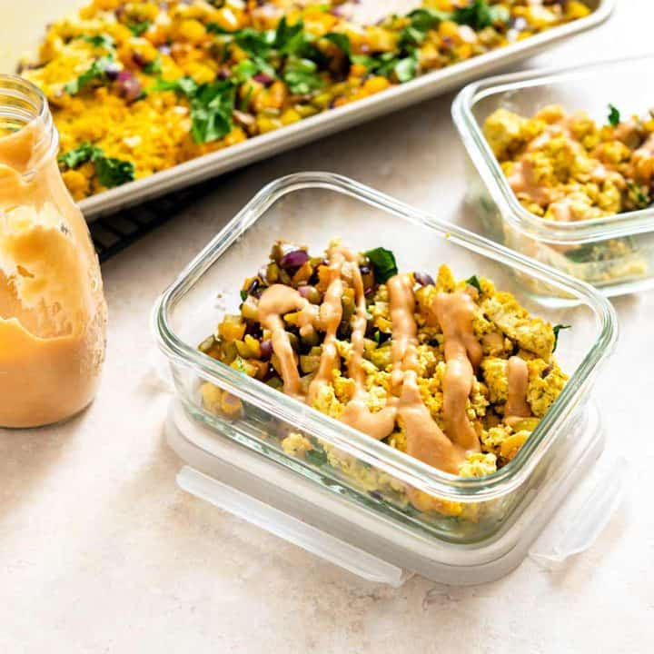 Two meal prep containers filled with Sheet Pan Tofu Scramble and hash, drizzled with sauce, next to a sheet pan