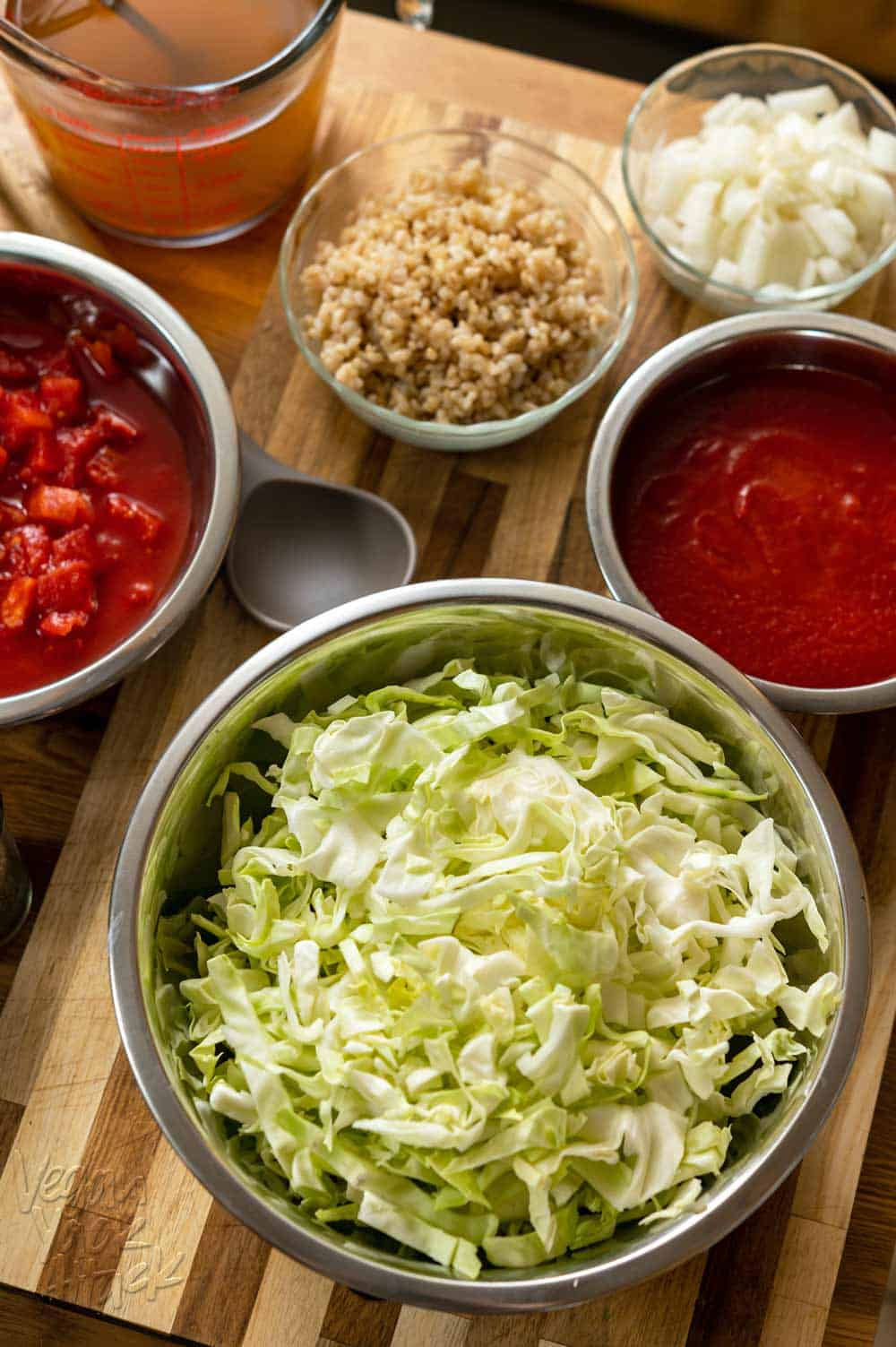 Ingredients in bowls on a cutting board, including cabbage, tomatoes, and rice