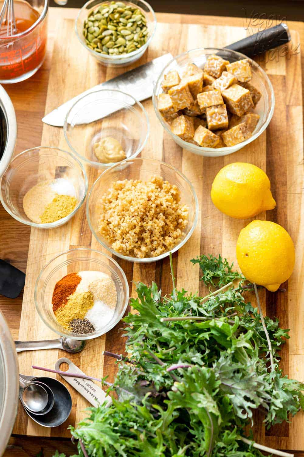 Ingredients such as tempeh, lemon, quinoa, spices, kale, and more laid out on a cutting board