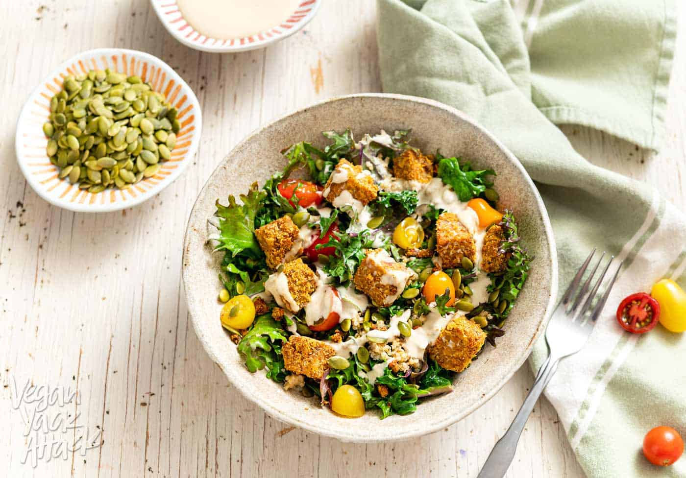Comforting Tempeh Kale Salad in a ceramic bowl next to a green linen and fork