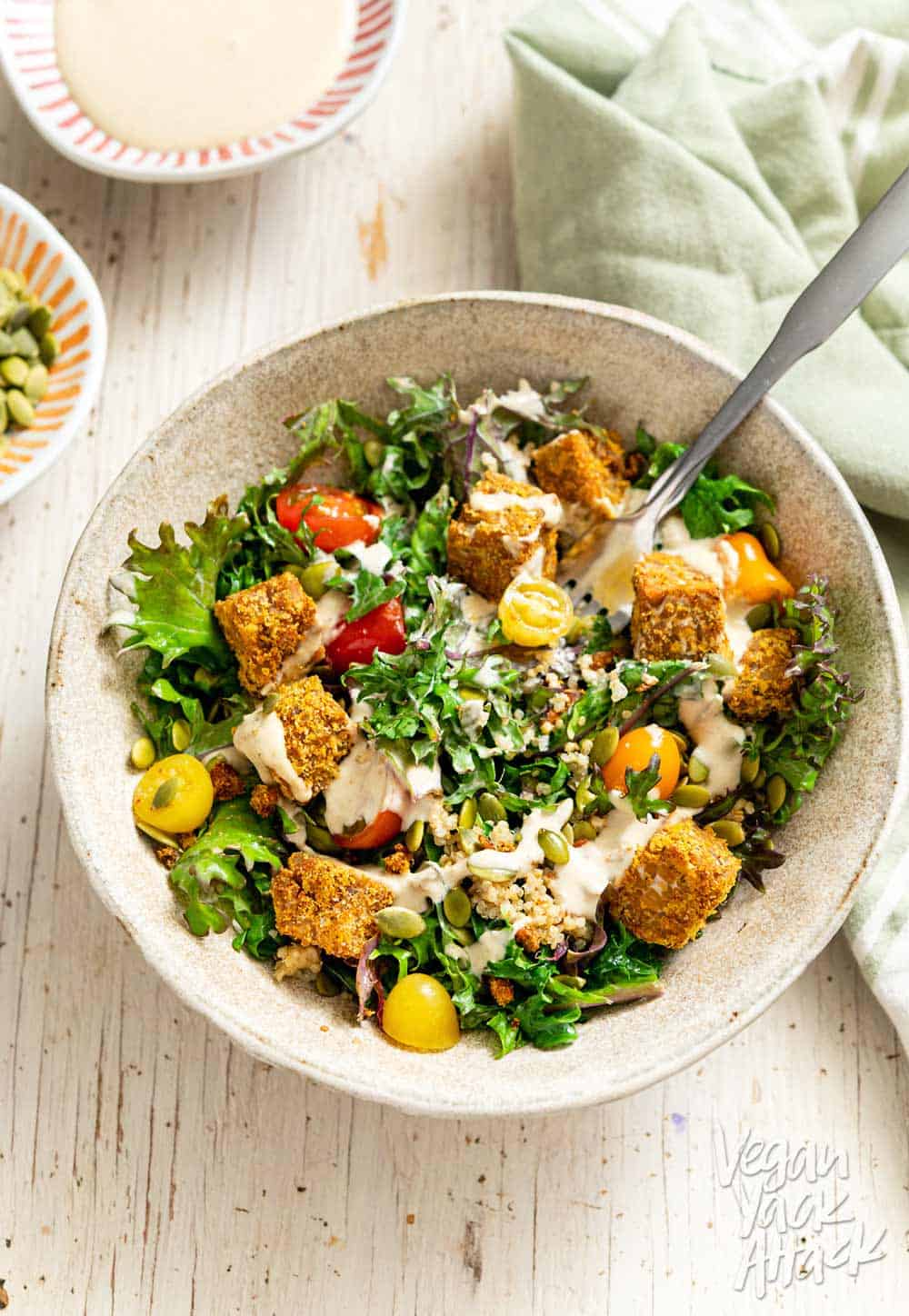 Close up shot of Comforting Tempeh Kale Salad in a ceramic bowl with fork