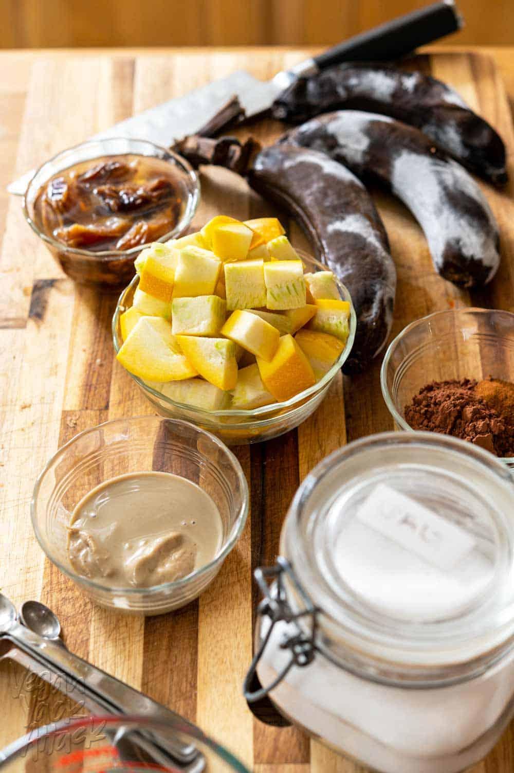 Squash, tahini, cocoa powder, salt, banana, dates, and salt on a cutting board