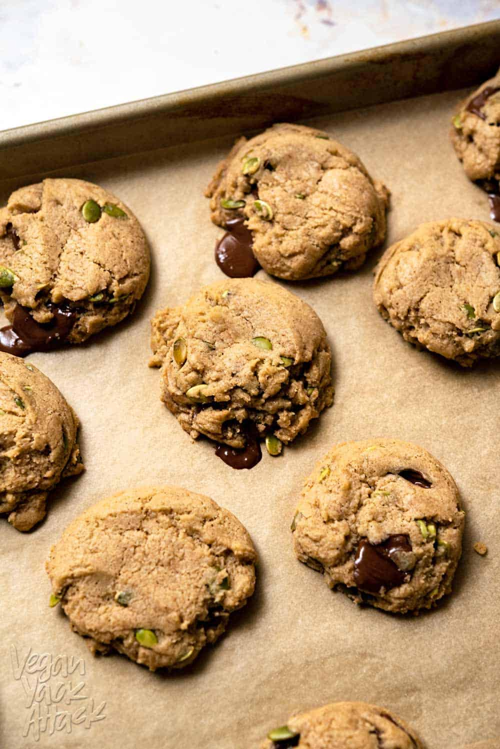 Freshly baked chocolate chai cookies on a parchment-lined baking sheet