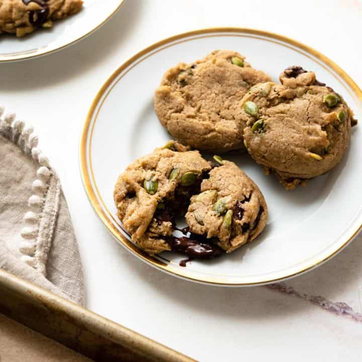 Cookies on a baking sheet with plate of cookies next to it