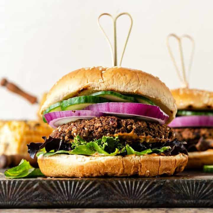 Grilled eggplant burger stacked with onion, cucumbers, mixed greens and bun