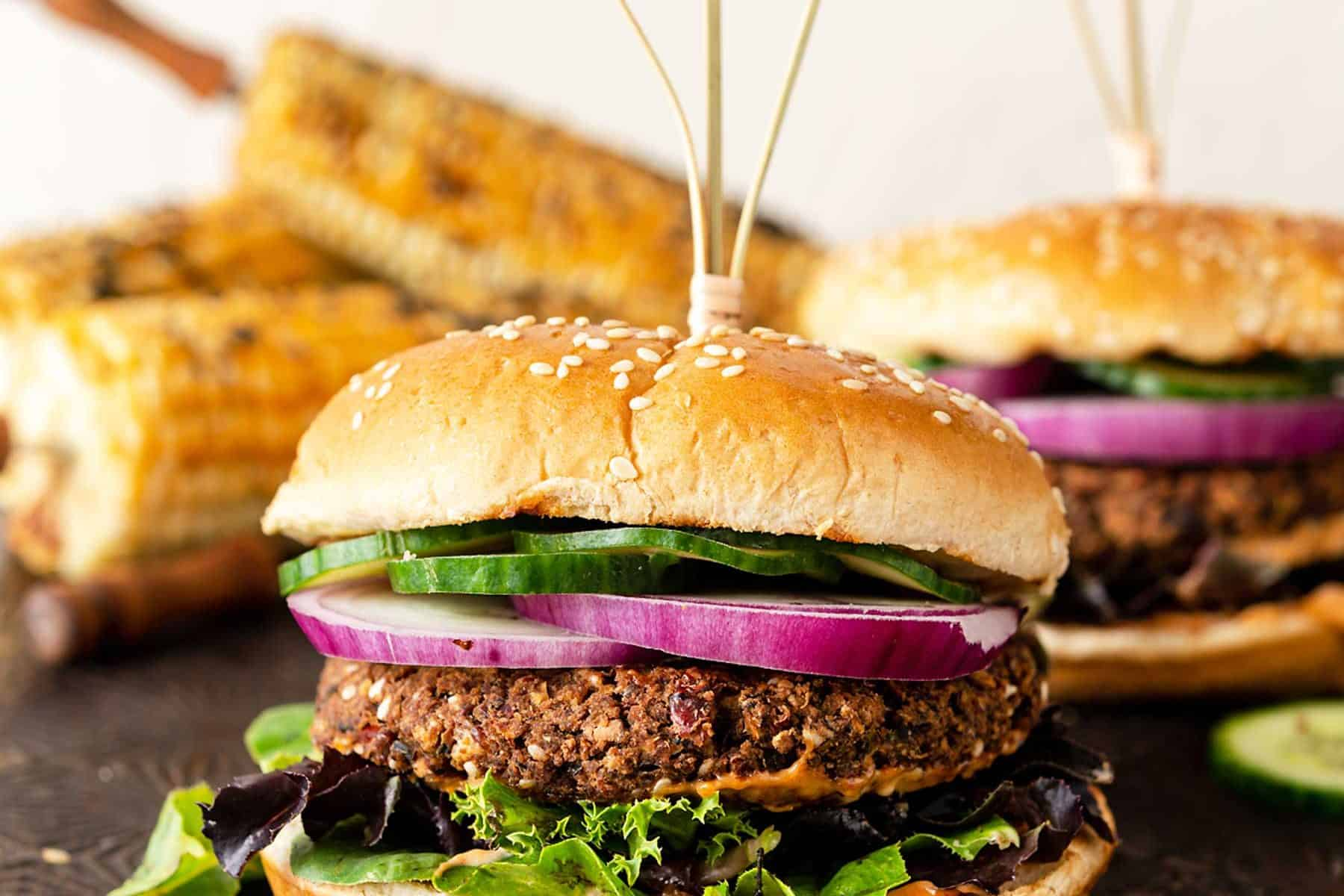 Veggie burger stacked with onion, cucumbers, mixed greens and bun